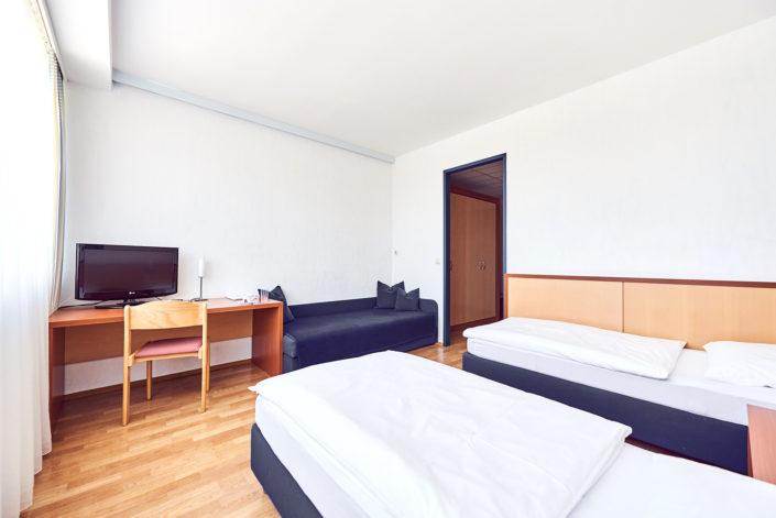 Hotelzimmer zwei Betten Fernseher hell freundlich